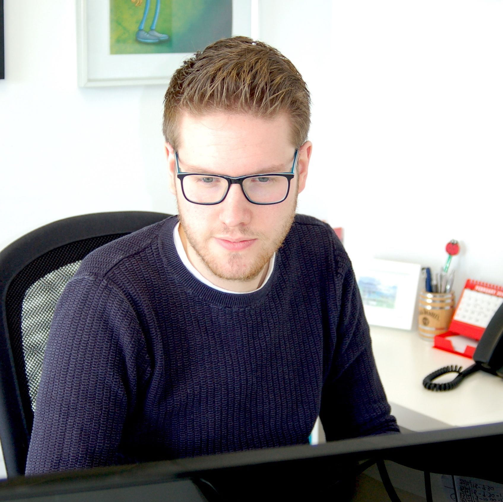 graphic designer working at a computer Luke Smith design ely Cambridgeshire